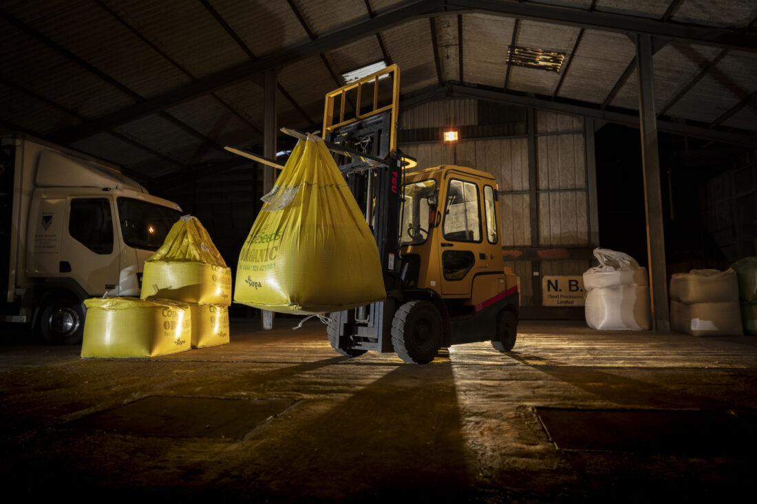Forklift in a barn lifting a bag of organic grain